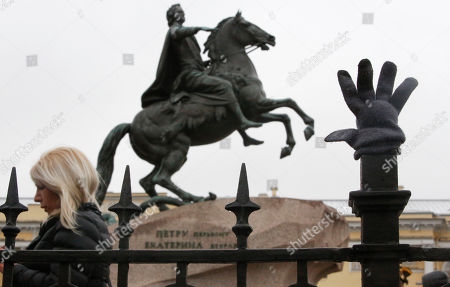 A lost glove hangs on a fence near a city landmarks, the equestrian statue of Peter the Great known as the Bronze Horseman by French sculptor Etienne Maurice Falconet in St.Petersburg, Russia