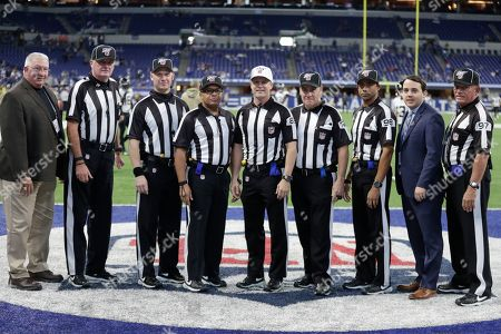 Game officials, second from left, are head linesman Ed Camp (134), back judge Rich Martinez (39), field judge James Coleman (95), back judge Shawn Hochuli (83), umpire Paul King (121), head linesman Greg Bradley (98) and field judge Tom Hill (97) pose for a photo before an NFL football game between the Jacksonville Jaguars and the Indianapolis Colts, in Indianapolis