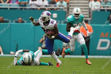 Devin Singletary #26 of Buffalo runs from Reshad Jones #20 and Bobby McCain #28 of Miami during the NFL football game between the Miami Dolphins and Buffalo Bills at Hard Rock Stadium in Miami Gardens FL. The Bills defeated the Dolphins 37-20