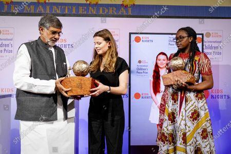 Stock Picture of Kailash Satyarthi (L), Children's rights activist from India presents the International Children's Peace Prize 2019 to climate activist Luisa Neubauer (R), as other prize winner peace activist Divina Maloum (R) from Cameroon looks on, in The Hague, The Netherlands, 20 November 2019. Neubauer accepted the prize on behalf of the Swedish teenage climate activist Greta Thunberg, who could not be present at the award ceremony.