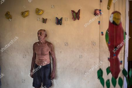"""Jose Calderon, 86, stands next to wall adornments given to him by neighbors in """"Los Hijos de Dios"""" neighborhood in Maracaibo, Venezuela, . Few in Maracaibo have responded to Venezuelan opposition leader Juan Guaido's efforts to reignite his movement, despite it being a city hard hit by crisis. Its residents endure daily power outages in a region that's punishingly hot"""