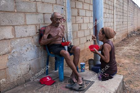 """Hayde Chacin and her husband Jose Calderon eat a lunch donated by neighbors in """"Los Hijos de Dios"""" neighborhood in Maracaibo, Venezuela, . Thanks to the generosity of neighbors, Chacin and Calderon are surviving their elderly years on the outskirts of Venezuela's second largest city of Maracaibo"""