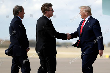 President Donald Trump greets Texas Lt. Gov. Dan Patrick as Attorney General Ken Paxton, left, watches as he arrives at Austin-Bergstrom International Airport for a visit to an Apple manufacturing plant, in Austin