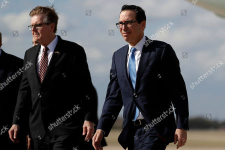 Texas Lt. Gov. Dan Patrick, left, walk with Treasury Secretary Steven Mnuchin as President Donald Trump arrives at Austin-Bergstrom International Airport for a visit to an Apple manufacturing plant, in Austin