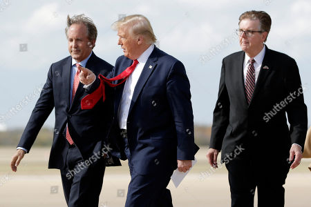 President Donald Trump walks with Texas Lt. Gov. Dan Patrick, right, and Texas Attorney General Ken Paxton, left, at Austin-Bergstrom International Airport for a visit to an Apple manufacturing plant, in Austin