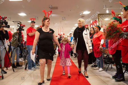 Five-year-old, Elizabeth Stanley, center arrives at Macy's Meadowood accompanied by Macy's Meadowood women's sales manager, Connie Yale, left, and Make-A-Wish® NECCANNV President and CEO Jennifer Stolo on in Reno, Nev. As part of Macy's Believe campaign, Macy's and Make-A-Wish® celebrate Wish Wednesday each week by granting the wishes of kids battling critical illnesses. Macy's Meadowood and Make-A-Wish® celebrate this Wish Wednesday by granting Elizabeth's wish to design a dress in New York City