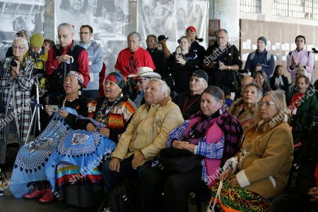 Sacheen Littlefeather, second from right in the front row, listens to ceremonies marking the 50th anniversary of the Native American occupation of Alcatraz Island, in San Francisco. About 150 people gathered at Alcatraz to mark the 50th anniversary of a takeover of the island by Native American activists. Original occupiers, friends, family and others assembled Wednesday morning for a program that included prayer, songs and speakers. They then headed to the dock to begin restoring messages painted by occupiers on a former barracks building. In 1973 Littlefeather represented Marlon Brando at the Oscars to decline his Best Actor award