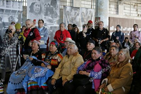 Stock Photo of Sacheen Littlefeather, second from right in the front row, listens to ceremonies marking the 50th anniversary of the Native American occupation of Alcatraz Island, in San Francisco. About 150 people gathered at Alcatraz to mark the 50th anniversary of a takeover of the island by Native American activists. Original occupiers, friends, family and others assembled Wednesday morning for a program that included prayer, songs and speakers. They then headed to the dock to begin restoring messages painted by occupiers on a former barracks building. In 1973 Littlefeather represented Marlon Brando at the Oscars to decline his Best Actor award