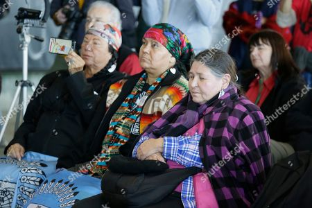 Stock Image of Sacheen Littlefeather, right, listens to ceremonies marking the 50th anniversary of the Native American occupation of Alcatraz Island, in San Francisco. About 150 people gathered at Alcatraz to mark the 50th anniversary of a takeover of the island by Native American activists. Original occupiers, friends, family and others assembled Wednesday morning for a program that included prayer, songs and speakers. They then headed to the dock to begin restoring messages painted by occupiers on a former barracks building. In 1973 Littlefeather represented Marlon Brando at the Oscars to decline his Best Actor award