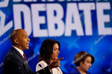 Democratic presidential candidate Sen. Cory Booker, D-N.J., left, speaks as Democratic presidential candidate Rep. Tulsi Gabbard, D-Hawaii, and Democratic presidential candidate Sen. Amy Klobuchar, D-Minn., right, listen during a Democratic presidential primary debate, in Atlanta