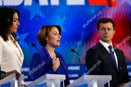 Democratic presidential candidate Sen. Amy Klobuchar, D-Minn., center speaks as Democratic presidential candidate Rep. Tulsi Gabbard, D-Hawaii, left and Democratic presidential candidate South Bend, Ind., Mayor Pete Buttigieg listen during a Democratic presidential primary debate, in Atlanta