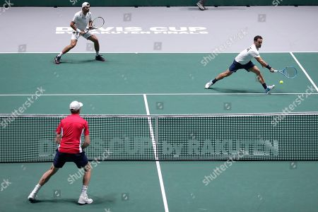 Stock Photo of Italy's Simone Bolelli and Fabio Fognini return the ball to US Sam Querrey and Jack Sock during their Davis Cup tennis match in Madrid, Spain