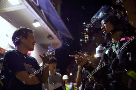 """A man argues with riot police in the Yuen Long area in Hong Kong, . More than 20 protesters inside a Hong Kong university campus surrendered to police on Thursday as the city's largest pro-Beijing political party urged voters to """"kick out the black force"""" in upcoming elections seen as a key gauge of public support for anti-government demonstrations"""