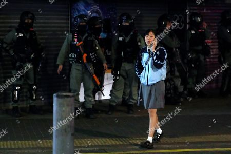"""A woman walks past riot police in the Yuen Long area in Hong Kong, . More than 20 protesters inside a Hong Kong university campus surrendered to police on Thursday as the city's largest pro-Beijing political party urged voters to """"kick out the black force"""" in upcoming elections seen as a key gauge of public support for anti-government demonstrations"""