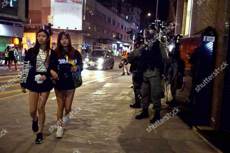 """Women walk past riot police in the Yuen Long area in Hong Kong, . More than 20 protesters inside a Hong Kong university campus surrendered to police on Thursday as the city's largest pro-Beijing political party urged voters to """"kick out the black force"""" in upcoming elections seen as a key gauge of public support for anti-government demonstrations"""