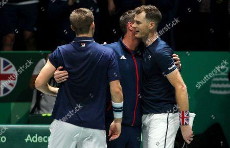Jamie Murray and Neal Skupski of Great Britain hug captain Leon Smith versus Kazakhstan