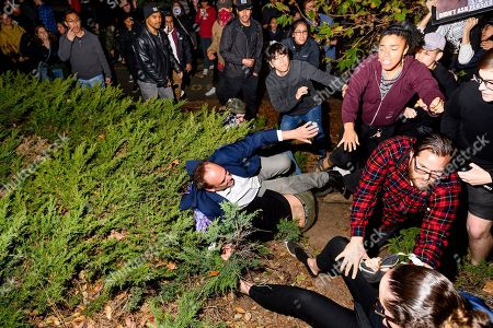 """Stock Picture of A man leaving a speech by conservative commentator Ann Coulter falls to the ground after being pushed by protesters at the University of California, Berkeley, in Berkeley, Calif. Hundreds of demonstrators gathered as Coulter delivered a talk titled """"Adios, America"""