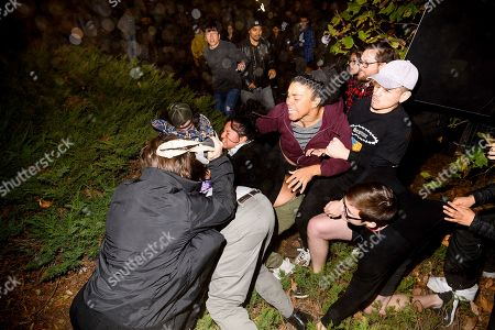 """Stock Photo of A man pushed by protesters is surrounded as he falls to the ground while leaving a speech by conservative commentator Ann Coulter at the University of California, Berkeley, in Berkeley, Calif. Hundreds of demonstrators gathered as Coulter delivered a speech titled """"Adios, America"""