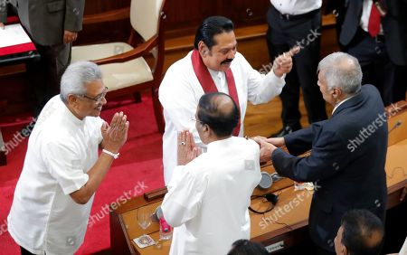 Sri Lankan President Gotabaya Rajapaksa, left, and new Prime Minister Mahinda Rajapaksa, center, interact with former Sri Lankan president Maithripala Sirisena, left back to camera, and former prime minister Ranil Wickremesinghe at the presidential secretariat in Colombo, Sri Lanka, . Wickremesinghe stepped down as prime minister earlier Thursday to clear the way for the president to form his government. Wickremesinghe said in a statement Wednesday that he is stepping down despite having a parliamentary majority, respecting the mandate Gotabaya Rajapaksa received in last Saturday's presidential election