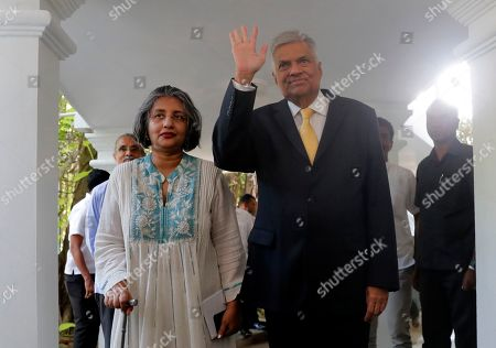 Sri Lanka's former prime minster Ranil Wickremesinghe waves to the media as he leaves his official residence with his wife Maitree in Colombo, Sri Lanka, . Wickremesinghe stepped down as prime minister earlier Thursday to clear the way for the president to form his government. Wickremesinghe said in a statement Wednesday that he is stepping down despite having a parliamentary majority, respecting the mandate Gotabaya Rajapaksa received in last Saturday's presidential election