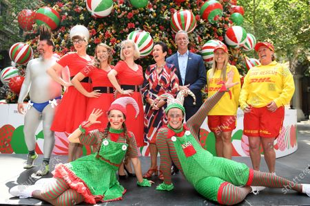 Sydney Lord Mayor Clover Moore and Surf Life Saving NSW CEO Steven Pearce pose for a photograph with DJ Peter Baecker (left) the Jingle Belles and roving elves at the announcement of the city's Christmas program in front of the Christmas tree at Martin Place in Sydney, Australia, 21 November 2019.