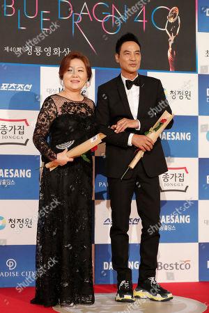 Simon Yam, Kim Hye-sook. Hong Kong actor Simon Yam, right, and South Korean actress Kim Hye-sook pose for photographers upon their arrival at the 40th Blue Dragon Film Awards in Incheon, South Korea