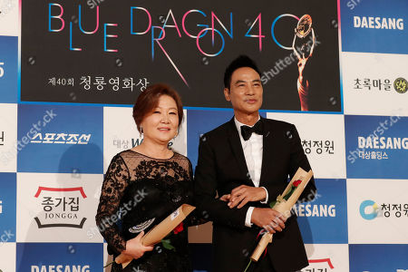 Stock Photo of Simon Yam, Kim Hye-sook. Hong Kong actor Simon Yam, right, and South Korean actress Kim Hye-sook pose for photographers upon their arrival at the 40th Blue Dragon Film Awards in Incheon, South Korea