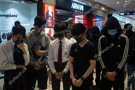 Pro-democracy protesters observe a moment of silence during a sit in at a mall in Yuen Long, Hong Kong, China, 21 November 2019. The protesters were marking the fourth month since an assault carried out by a group of white-clad men targeted protesters and passengers in the Yuen Long MTR station on 21 July 2019. Hong Kong is in its sixth month of mass protests, which were originally triggered by a now withdrawn extradition bill, and have since turned into a wider pro-democracy movement.