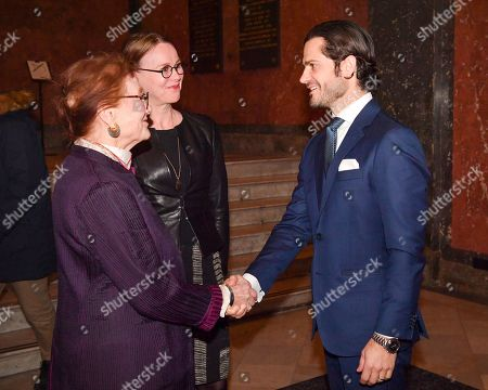 Sweden's Prince Carl Philip (R) is received by Susanna Pettersson (L), Superintendent at National museum, and Ann Westin (C), Chairwoman of the Bengt Julin foundation, at National museum