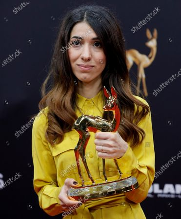 Iraqi human rights activist Nadia Murad poses with her 'courage' award at the 71st annual Bambi awards ceremony in Baden Baden, Germany, 21 November 2019. The awards recognize excellence in international media and television.