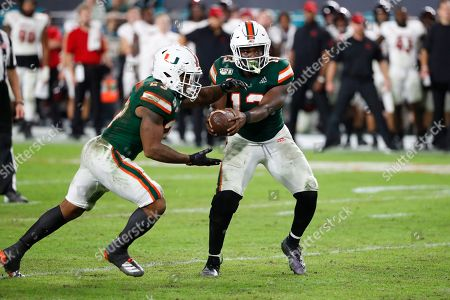 Miami running back DeeJay Dallas (13) hands off to running back Cam'Ron Harris (23) during the second half of an NCAA college football game, in Miami Gardens, Fla. Miami defeated Louisville 52-27