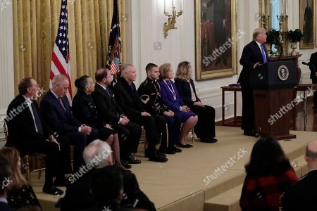 President Donald Trump speaks during a National Medal of Arts and National Humanities Medal ceremony in the East Room of the White House, in Washington. The honorees are from left, Arthur James Patterson, Chef Patrick O'Connell, Teresa Lozano Long, Ryan Williams, Jon Voight, Stf Sgt. Yon Kuh-newtzen, Sharon Percy Rockefeller and Allison Krauss