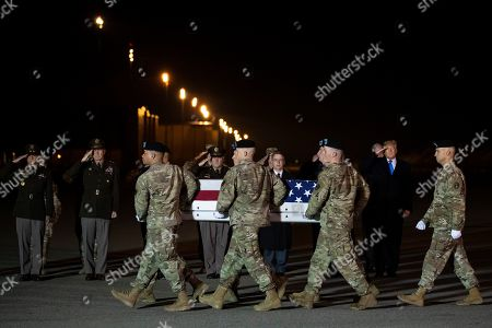President Donald Trump looks on as a U.S. Army carry team moves a transfer case containing the remains of Chief Warrant Officer 2 Kirk T. Fuchigami Jr., of Keaau, Hawaii, who according to the Department of Defense died in Afghanistan, during a casualty return ceremony, in Dover Air Force Base, Del