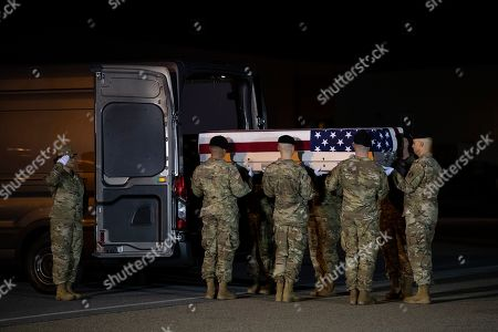 President Donald Trump and first lady Melania Trump watch as a U.S. Army carry team moves a transfer case containing the remains of Chief Warrant Officer 2 Kirk T. Fuchigami Jr. of Keaau, Hawaii, at Dover Air Force Base, Del. According to the Department of Defense, Fuchigami died in Afghanistan when his helicopter crashed while providing security for troops on the ground in eastern Logar Province