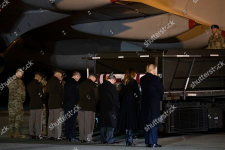 Donald Trump, Melania Trump. President Donald Trump and first lady Melania Trump, along with other members of the official party, pray in front of the transfer cases containing the remains of Chief Warrant Officer 2 David C. Knadle, of Tarrant, Texas, and Chief Warrant Officer 2 Kirk T. Fuchigami Jr., of Keaau, Hawaii, who according to the Department of Defense died in Afghanistan, during a casualty return ceremony, in Dover Air Force Base, Del