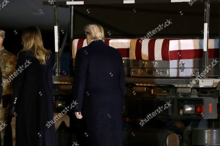 President Donald Trump and first lady Melania Trump walk past the transfer cases containing the remains of Chief Warrant Officer 2 David C. Knadle, of Tarrant, Texas, and Chief Warrant Officer 2 Kirk T. Fuchigami Jr. of Keaau, Hawaii, during a casualty return, at Dover Air Force Base, Del. According to the Department of Defense, Knadle died in Afghanistan when his helicopter crashed while providing security for troops on the ground in eastern Logar Province