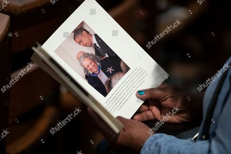 A person looks through the program before the start of the Celebration of the Life of Toni Morrison, at the Cathedral of St. John the Divine in New York