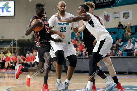 Coastal Carolina forward Isaac Hippolyte, right, and center Levi Cook (32) defend against Utah guard Both Gach (11) during the first half of an NCAA college basketball game at the Myrtle Beach Invitational in Conway, S.C