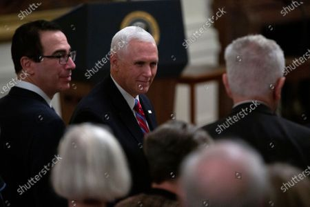 United States Vice President Mike Pence and United States Secretary of the Treasury Steven Mnuchin arrive to an East Room ceremony where United States President Donald Trump awarded Alison Krauss, Sharon Percy Rockefeller, the Musicians of the United States Military, Jon Voight, the Claremont Institute, Theresa Lozano Long, Patrick J. O'Connell, and James Patterson the National Medal of Arts and the National Humanities Medal