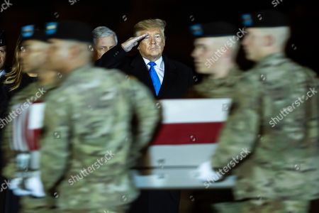 Donald Trump, Melania Trump. President Donald Trump watches as a U.S. Army carry team moves a transfer case containing the remains of Chief Warrant Officer 2 Kirk T. Fuchigami Jr. of Keaau, Hawaii, at Dover Air Force Base, Del. According to the Department of Defense, Fuchigami died in Afghanistan when his helicopter crashed while providing security for troops on the ground in eastern Logar Province