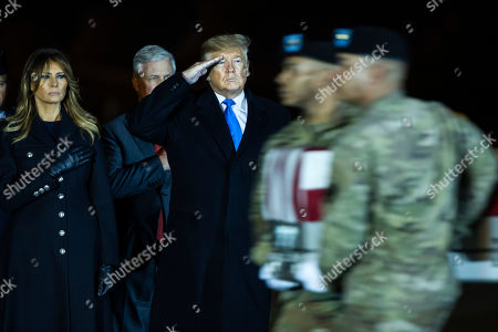 Donald Trump, Melania Trump. President Donald Trump and first lady Melania Trump watch as a U.S. Army carry team moves a transfer case containing the remains of Chief Warrant Officer 2 Kirk T. Fuchigami Jr. of Keaau, Hawaii, at Dover Air Force Base, Del. According to the Department of Defense, Fuchigami died in Afghanistan when his helicopter crashed while providing security for troops on the ground in eastern Logar Province