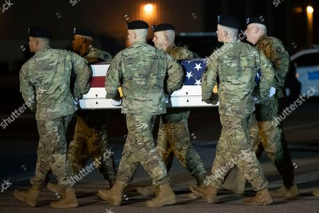 A U.S. Army carry team moves a transfer case containing the remains of Chief Warrant Officer 2 Kirk T. Fuchigami Jr. of Keaau, Hawaii, at Dover Air Force Base, Del. According to the Department of Defense, Fuchigami died in Afghanistan when his helicopter crashed while providing security for troops on the ground in eastern Logar Province
