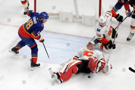 Calgary Flames goaltender David Rittich, of the Czech Republic, falls on the puck as teammate Michael Stone (26) and St. Louis Blues' Robert Thomas (18) watch during the third period of an NHL hockey game, in St. Louis. The Blues won 5-0