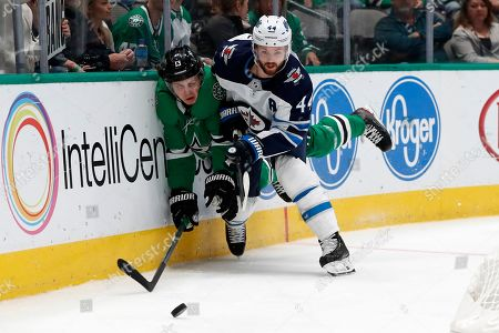 Mattias Janmark, Josh Morrissey. Dallas Stars center Mattias Janmark (13) is slammed against the boards by Winnipeg Jets defenseman Josh Morrissey (44) as the two compete for control of the puck in the first period of an NHL hockey game in Dallas