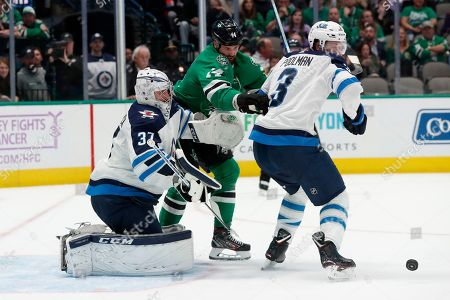 Stock Photo of Connor Hellebuyck, Tucker Poolman, Jamie Benn. Winnipeg Jets goaltender Connor Hellebuyck (37) and defenseman Tucker Poolman (3) defend against pressure from Dallas Stars left wing Jamie Benn (14) on an attack in the first period of an NHL hockey game in Dallas