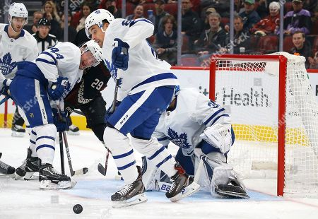 Toronto Maple Leafs defenseman Cody Ceci, right, goes after the puck as Maple Leafs defenseman Morgan Rielly (44) and Arizona Coyotes center Barrett Hayton (29) battle during the first period of an NHL hockey game, in Glendale, Ariz