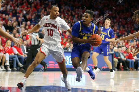 South Dakota State guard Brandon Key, front right, drives past Arizona guard Jemarl Baker Jr. (10) in the first half during an NCAA college basketball game, in Tucson, Ariz