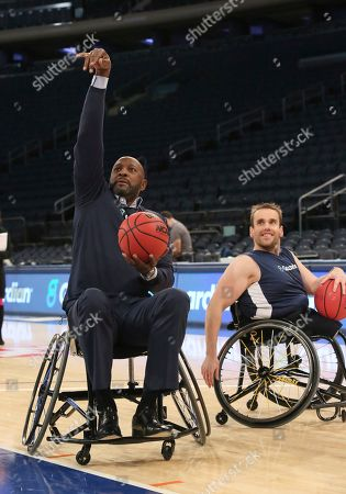 Basketball legend Alonzo Mourning gets some pointers from Ryan Martin, from CUNY's Inclusive Sports basketball program, on how to sink a shot from a wheelchair as part of Guardian's game of HORSE to showcase that Disability Doesn't Mean Inability during the 2K Empire Classic at Madison Square Garden on in New York