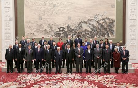 Chinese President Xi Jinping, center, and Vice Premier Liu He, fifth left, attend a group photo event with former U.S. Secretary of State Henry Kissinger, left to Xi, former U.S. Treasury Secretary Henry Paulson, right to Xi, and members of a delegation from the 2019 New Economy Forum before a meeting at the Great Hall of the People in Beijing