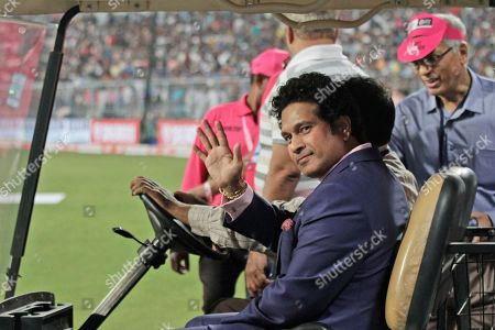 Former Indian cricketer Sachin Tendulkar acknowledges the crowd during a grand parade of India's former cricket captains during the first day of the second test match between India and Bangladesh, in Kolkata, India